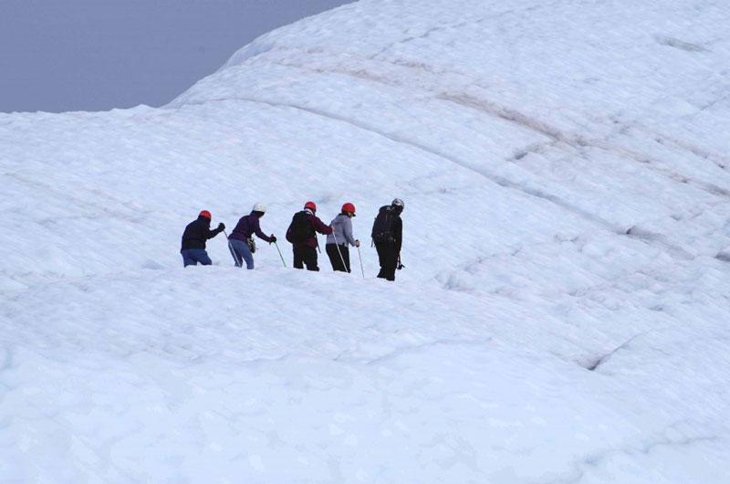Vorsicht geboten: Mit unsicheren Schritten gehen die Touristen über das Eis des Gletschers.