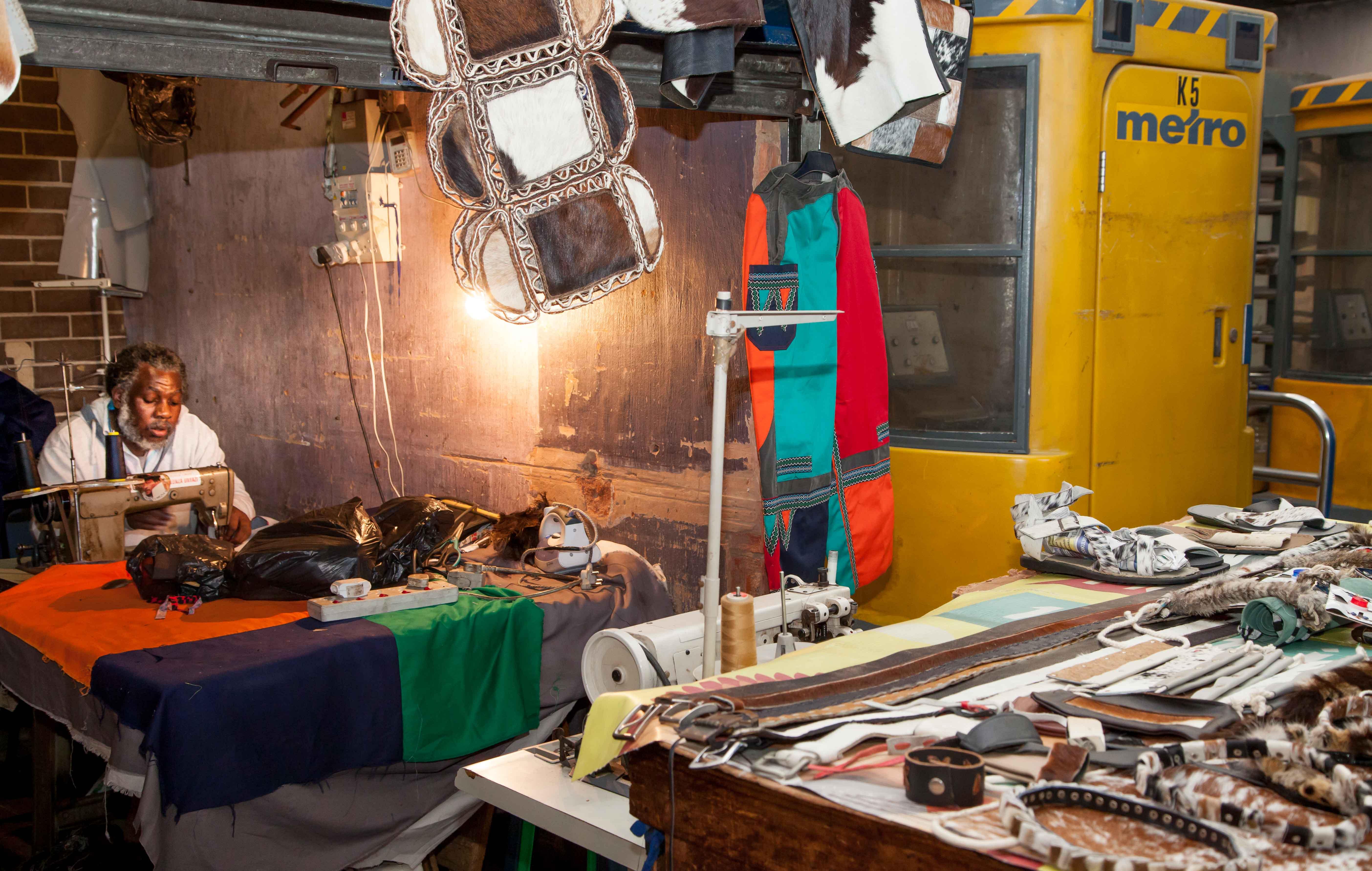 In einer dunklen Ecke direkt neben dem Eingang zur Metro hat dieser Mann seine Reparaturwerkstatt für Lederwaren.