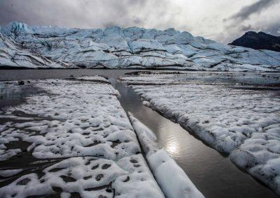 Durch dichte Wolken dringt die Sonne und spiegelt sich im Gletschersee.
