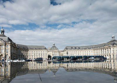 Der Börsenplatz von Bordeaux und die Straßenbahn spiegeln sich im miroir d'eau an der Garonne.