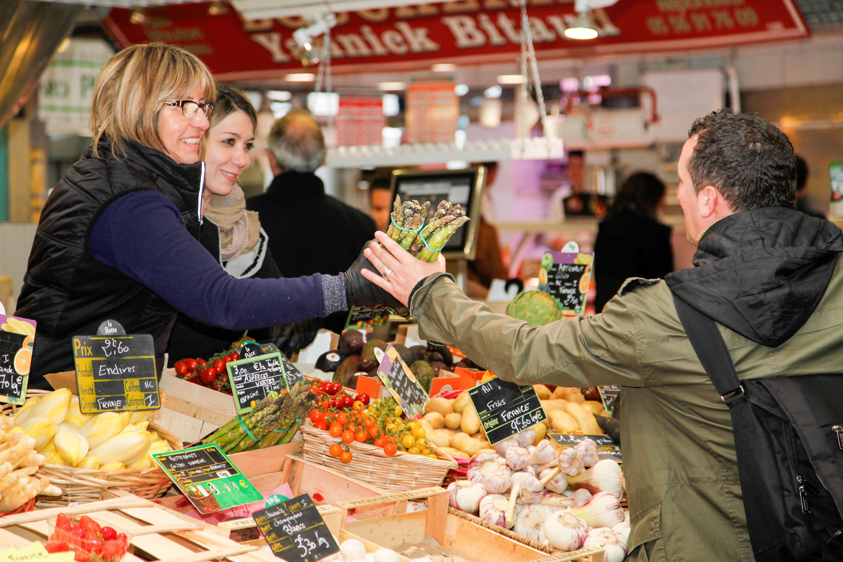 Früchte und Gemüse im Überfluss auf dem Marche du Capucin in Bordeaux. Eine Verkäuferin reicht einem Kunden einen Bund Spargel.
