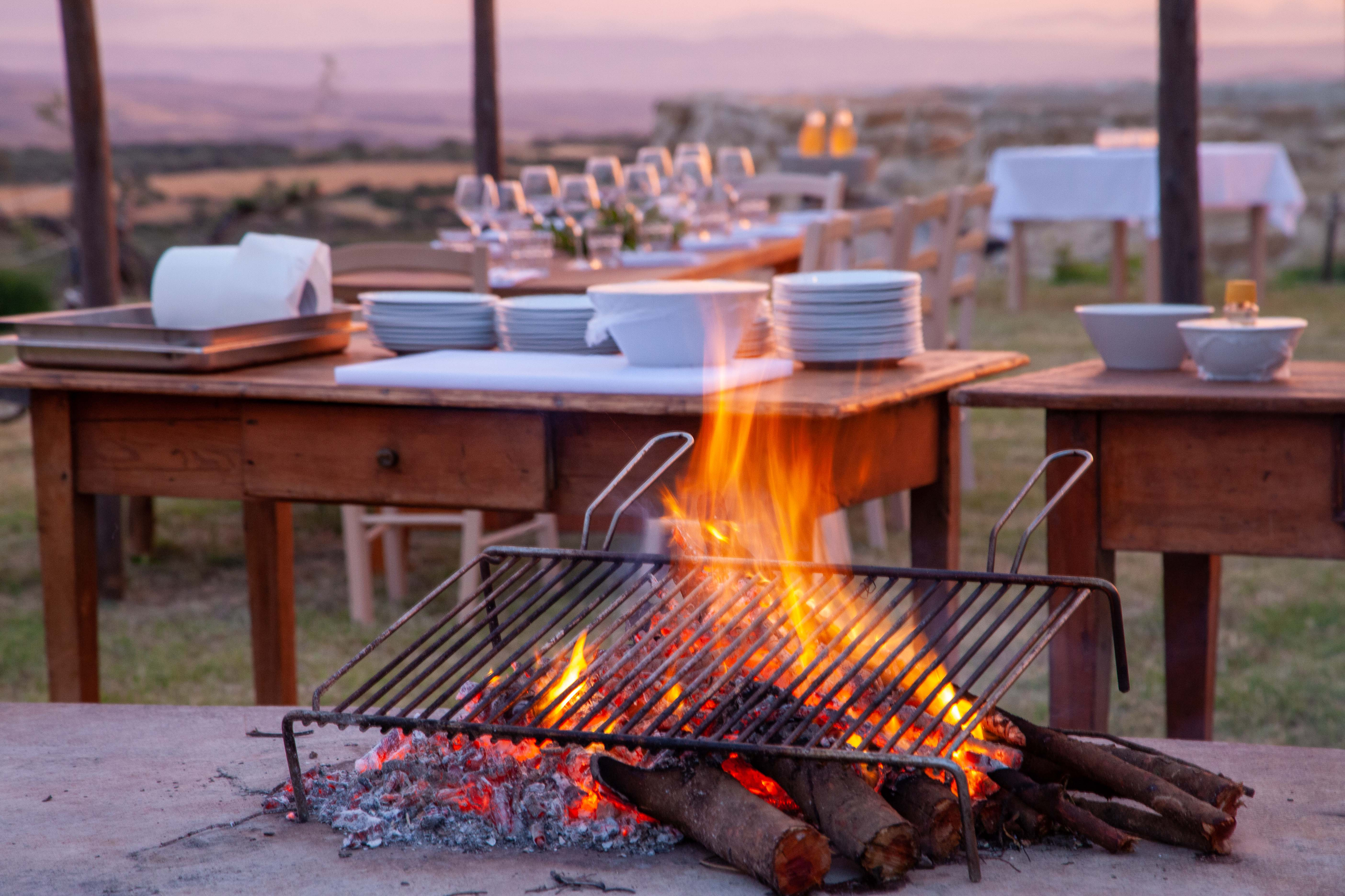 Vor dem Grill über offenem Feuer ist der Tisch zum Abendessen gedeckt.n.