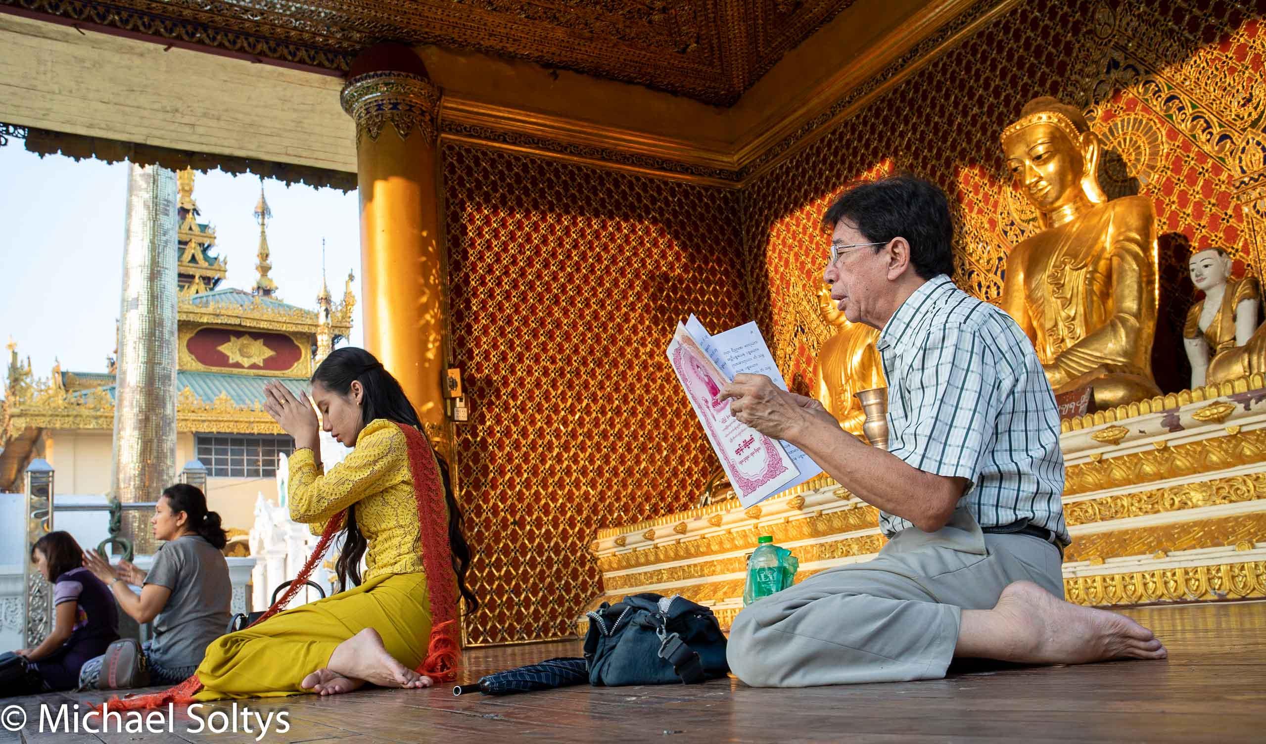 Vor einer Darstellung Buddhas in Gold beten Gläubige in der Shwedagon-Pagode.