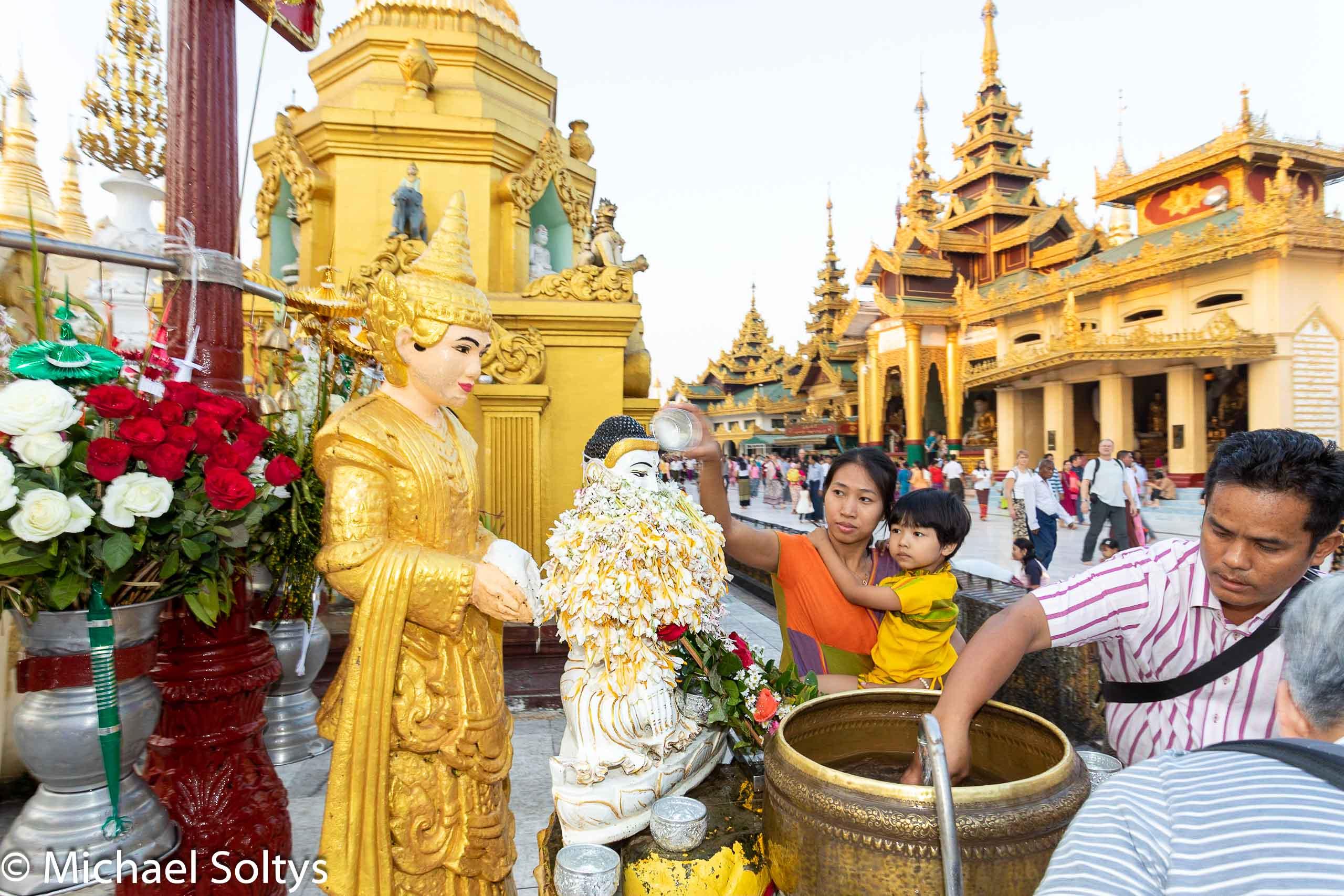 Eine Mutter und ihr Kind reinigen symbolisch eine blumengeschmückte Buddha-Figur.