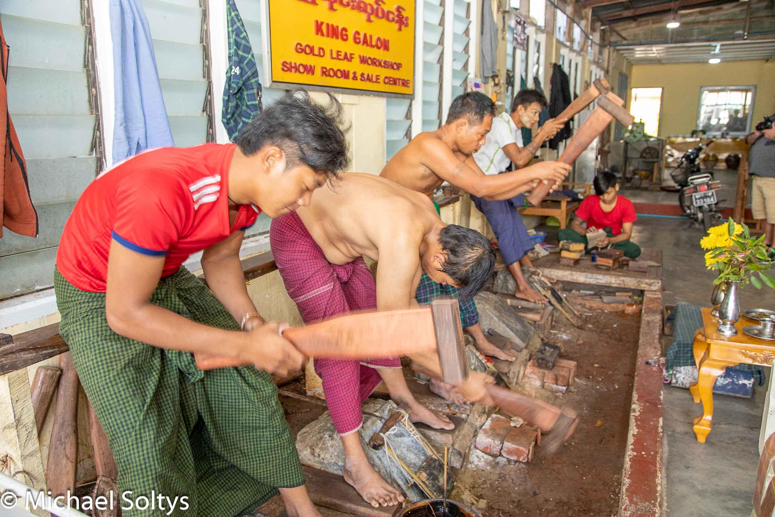 Knochenarbeit. Vier Männer schlagen das Gold zwischen ihren Füßen zu Blattgold.